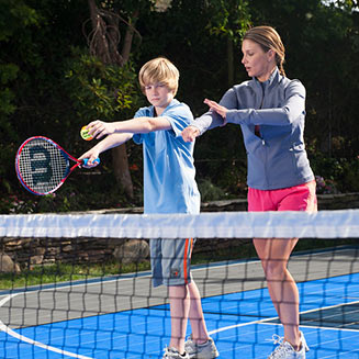 mom teaches son tennis on Sport Court surface