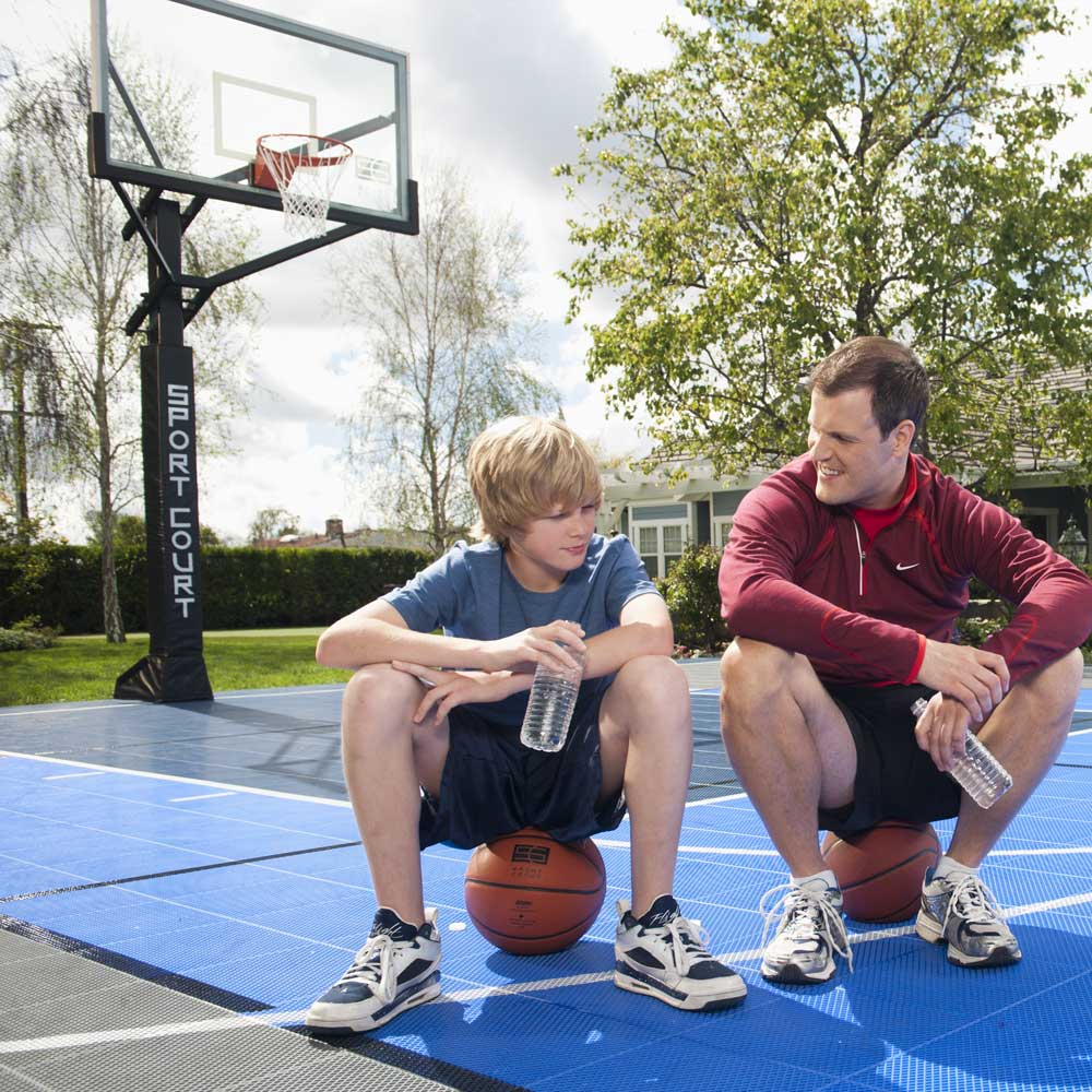dad and son sitting on basketballs talking on sport court backyard court