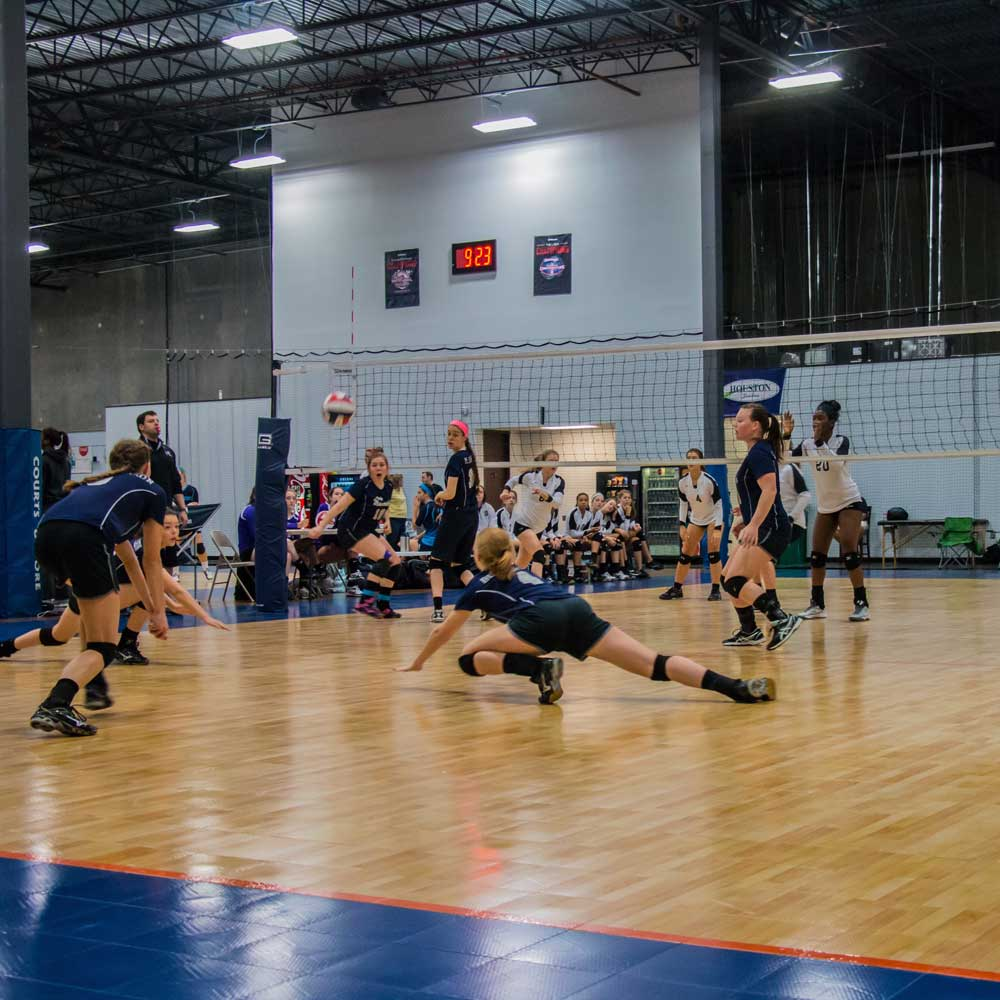 girls diving for volleyball on sport court flooring