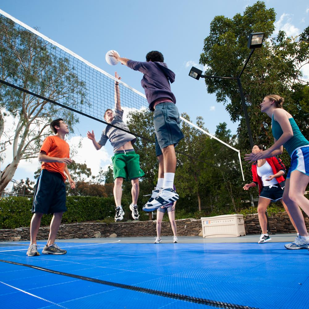 group of kids playing volleyball on outdoor sport court surface