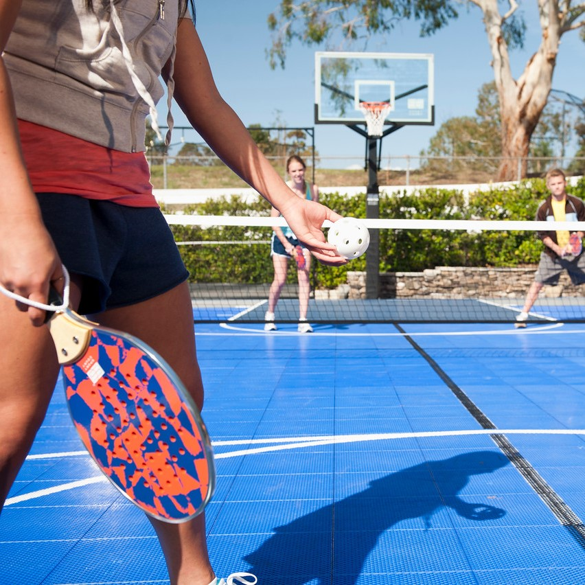 kids playing pickleball on sport court outdoor surface
