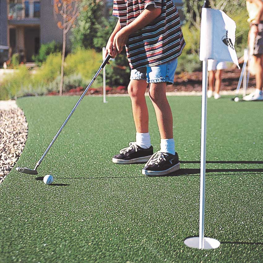 young boy putting golf ball on sport court synthetic turf