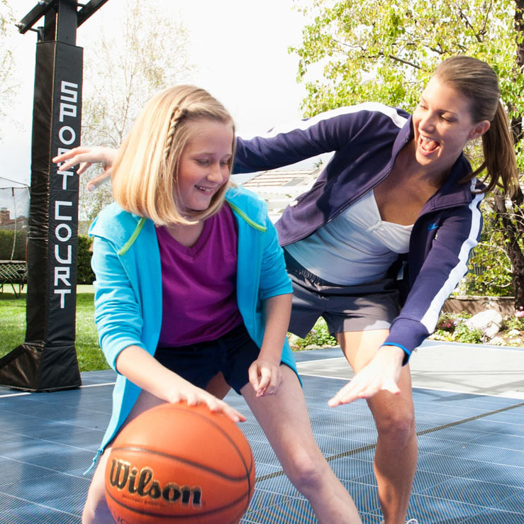 mom and daughter play on backyard basketball court