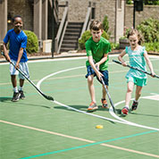 children play roller hockey on a Sport Court outdoor court