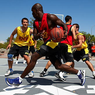 pro athletes playing basketball on sport court outdoor surface