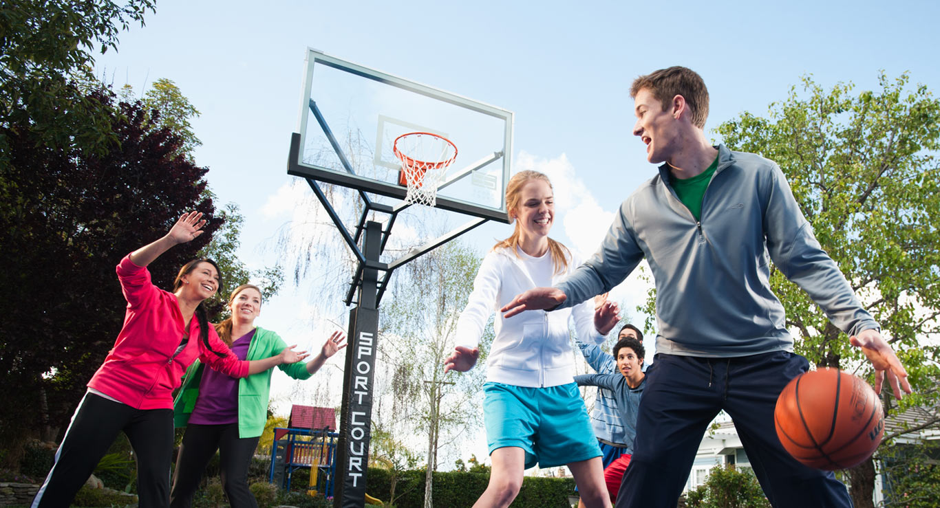 family playing basketball on outdoor home basketball court