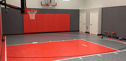indoor home gym with red wall pads and sport court surface